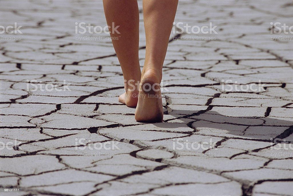 Woman walking barefoot across cracked earth royalty-free stock photo