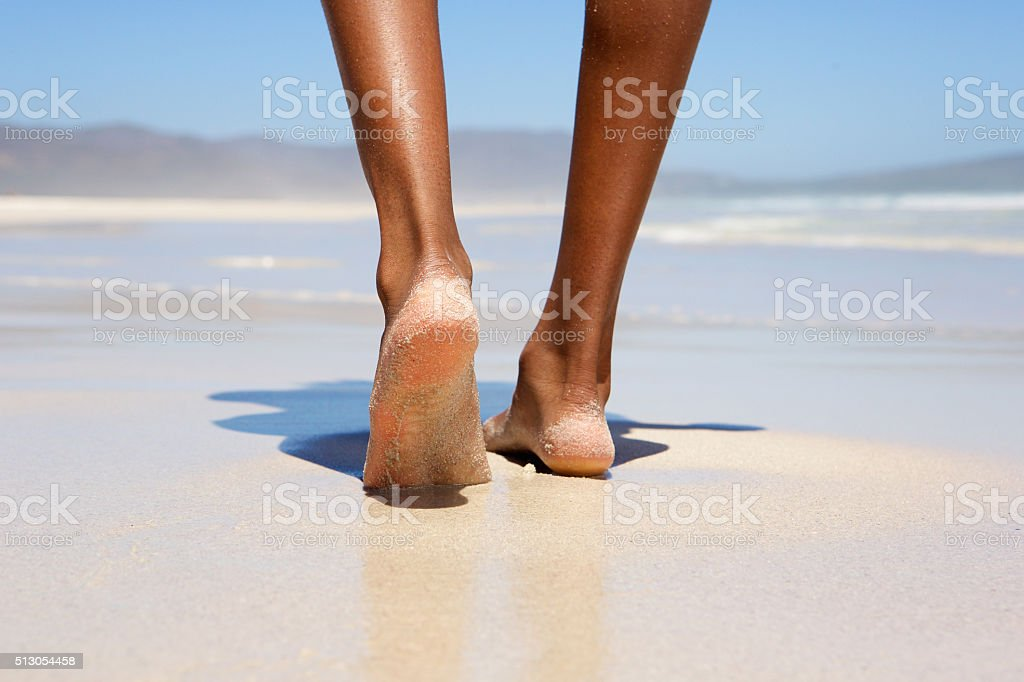 Woman walking barefoot on beach stock photo