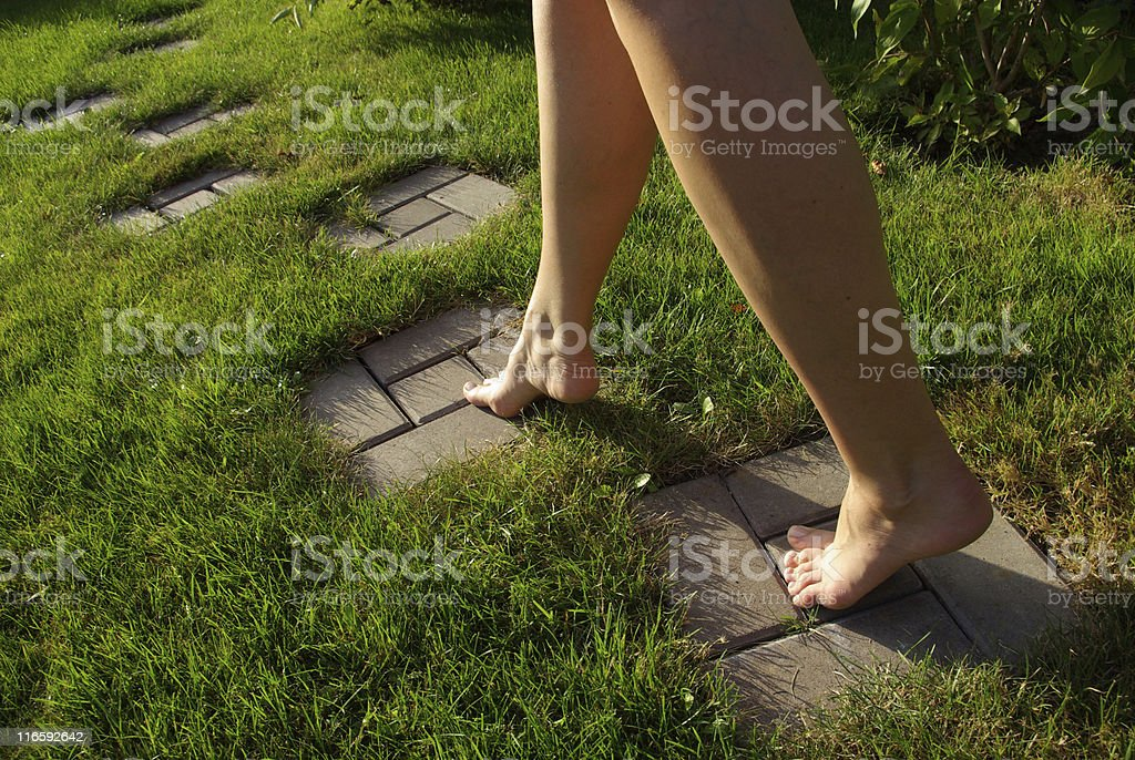 Woman walking barefoot on stepping stones in grass stock photo