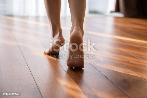 Close up of exhausted businesswoman touch massage foot suffer from uncomfortable heels shoes at work, tired unwell female feel discomfort in legs, relieve pain from feet ache, have strained muscle