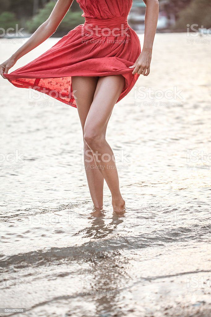 Woman walking barefoot on wet sea shore stock photo