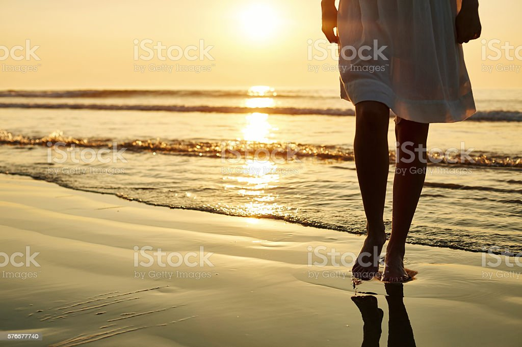 Woman walking barefoot on wet shore during sunset stock photo