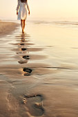 Rear view of woman walking barefoot in distance on wet sand. Female in sundress is leaving her footprints on shore. Low section of woman spending leisure time on beach at sunset.