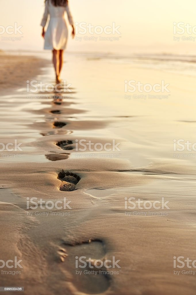 Woman walking barefoot on wet shore leaving footprints in sand stock photo