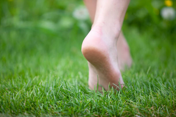 woman walking barefoot - scalzo foto e immagini stock