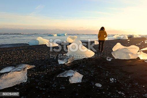 istock Woman Walking Between Icebergs on Lava Beach near Jokulsarlon Iceland 500264552