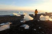Woman Walking Between Icebergs on Lava Beach near Jokulsarlon Iceland