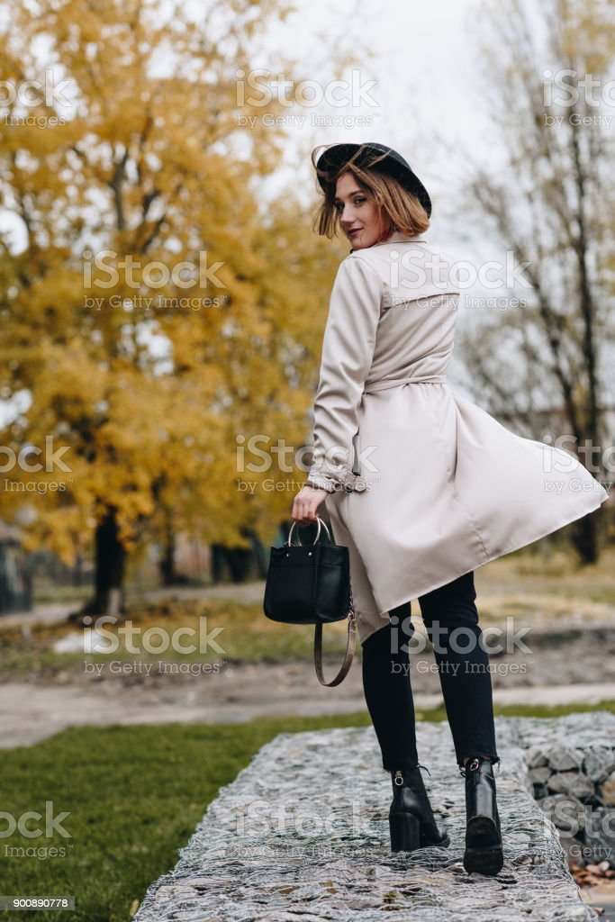 woman walking by autumn park stock photo