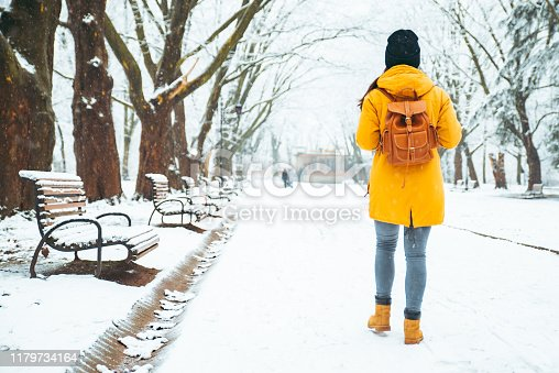 woman walking by snowed city park. view from behind. backpack. winter concept