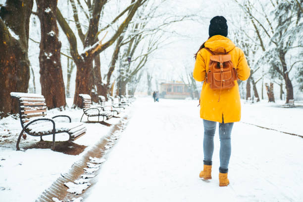 woman walking by snowed city park. view from behind. backpack. winter concept stock photo