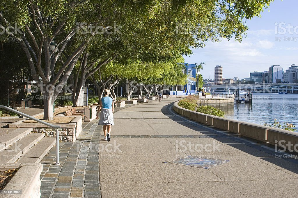woman walking by the river stock photo