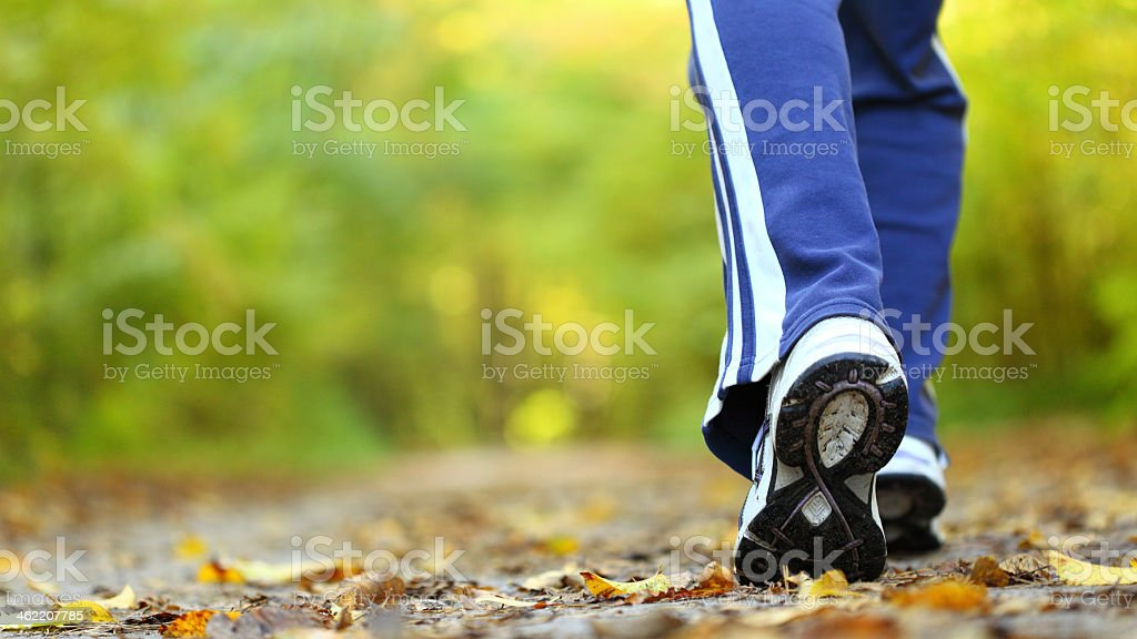A woman walking cross country in the autumn stock photo