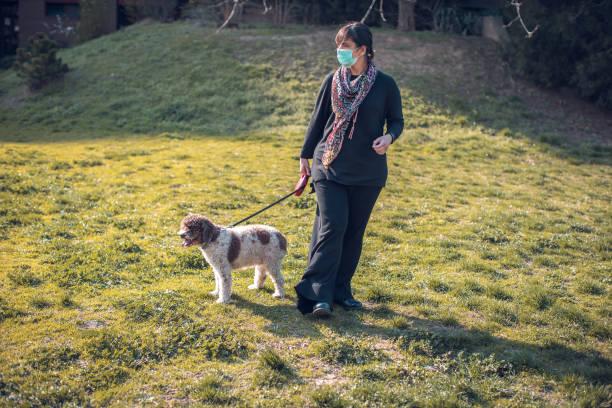 Woman walking dog in the park with face mask picture id1214594214?b=1&k=6&m=1214594214&s=612x612&w=0&h=6ekv7hm nmcev jpbxwxvedbywjf6hjc9zlcbpnwab8=