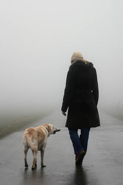 Woman Walking Dog on Misty Cold Day