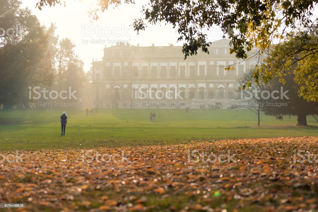 Woman walking down a green meadow at sunset with the Villa Reale of Monza in the background, Italy stock photo