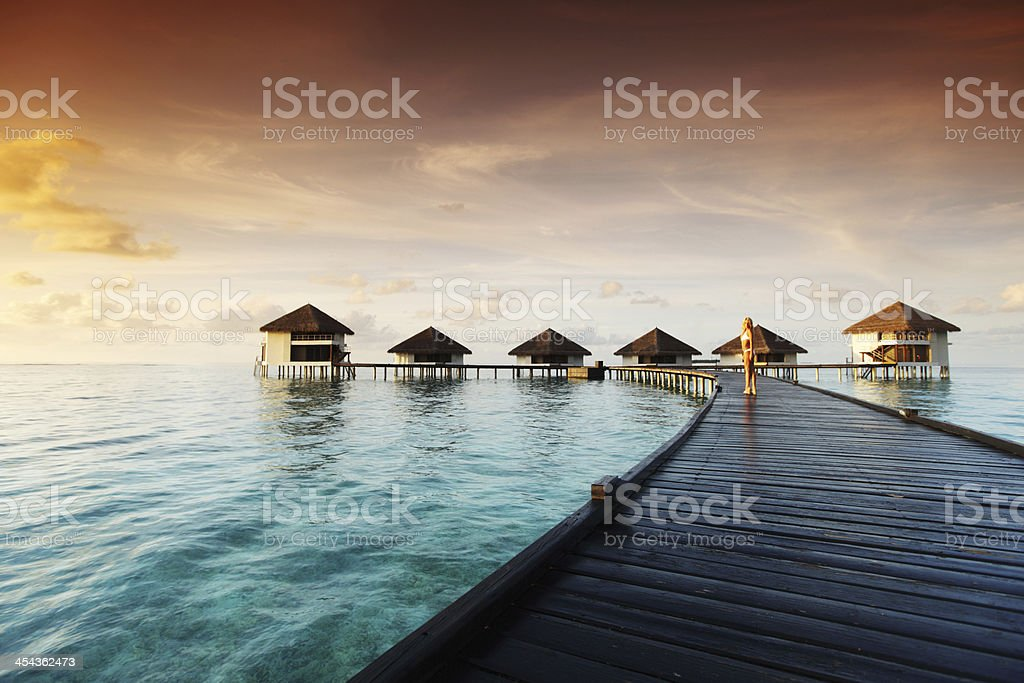 A woman walking down a wooden dock at a Maldivian resort stock photo