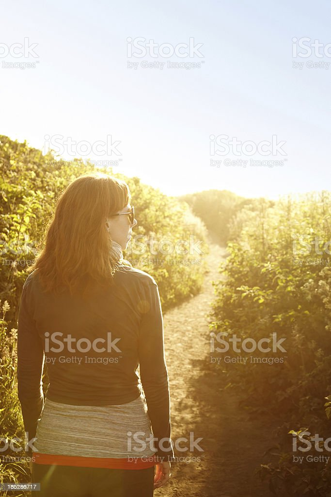 Woman walking down pathway in nature royalty-free stock photo