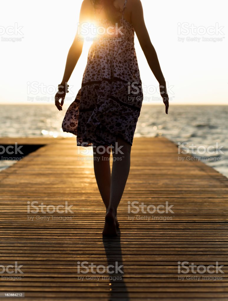 A woman walking down the board walk during sunset stock photo