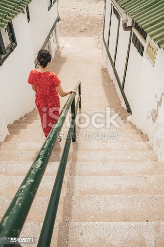 Woman walking down the stairs in El Garraf