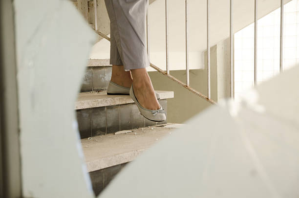Woman walking down the stairs stock photo