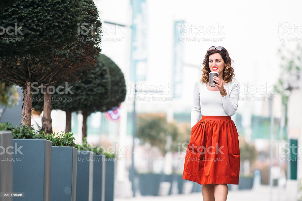 Woman walking down the street and drink coffee to go stock photo