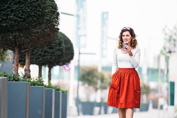 kobieta spaceru wzdłuż ulicy i pić kawę na wynos - spódnica zdjęcia i obrazy z banku zdjęć