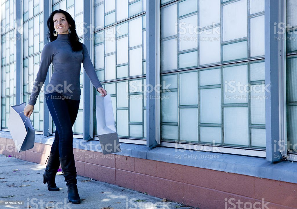 woman walking down the street carrying shopping bags stock photo