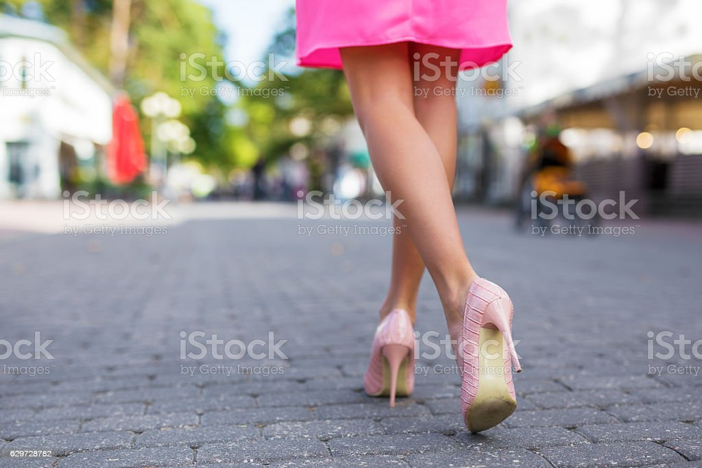 Woman walking down the street in high heels stock photo