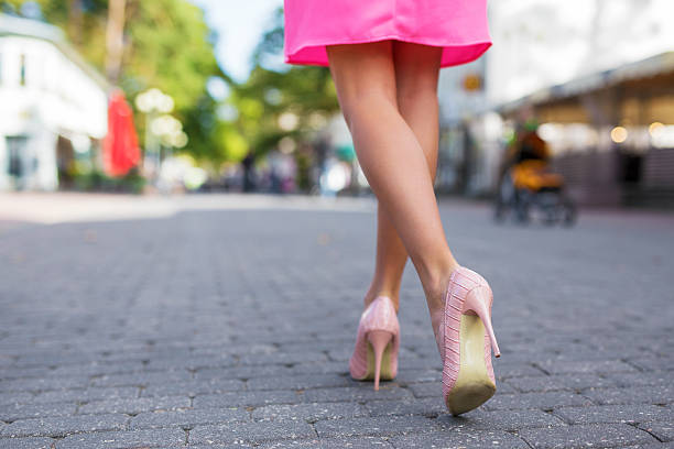 woman walking down the street in high heels - damen rock pink stock-fotos und bilder