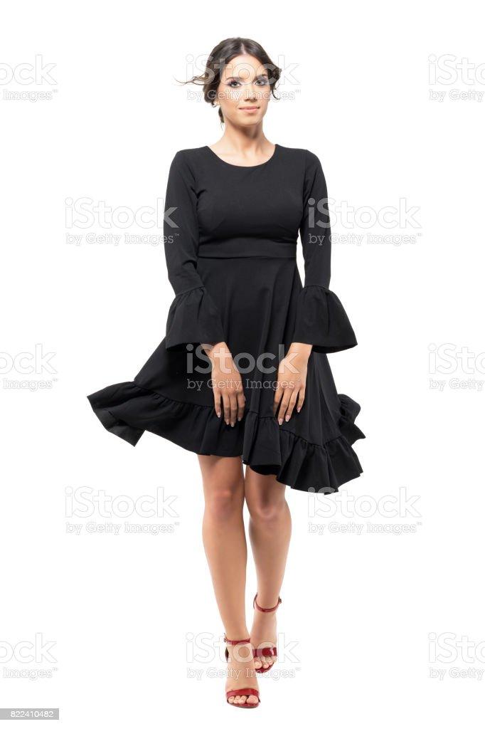 28100d7039af40 Vrouw lopen van de voorkant houden zwarte vliegen jurk met waait de wind in  de haren