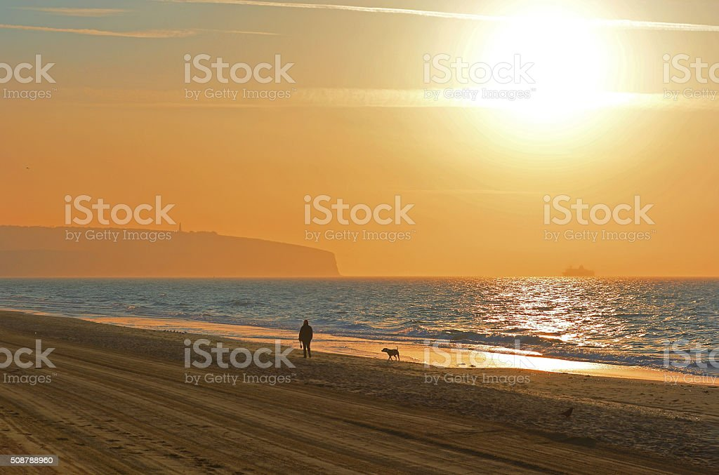 Woman Walking Her Dog At Sunrise A woman walking her dog along the beach at sunrise with sunlight reflecting from the water. In the background is a cliff and a ship can be seen in the distance. The beach in the foreground has been freshly cleaned creating a perfect setting for a travel location or holiday destination. Adult Stock Photo