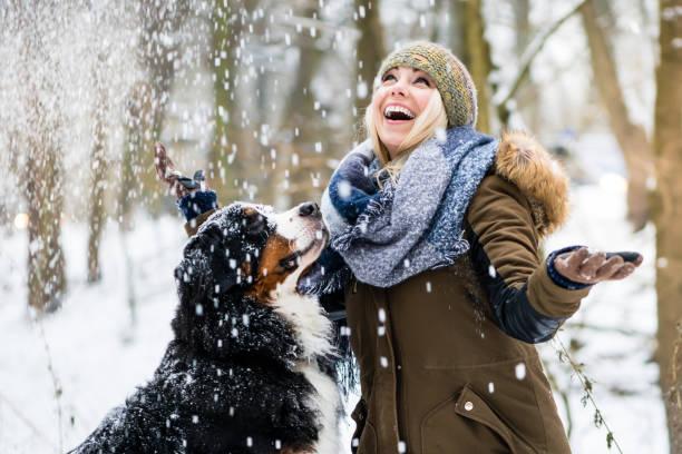 Frau zu Fuß ihren Hund in den Winter und erkunden Schnee gemeinsam – Foto