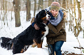 istock Woman walking her dog in the winter and both explore the snow together 1067461992