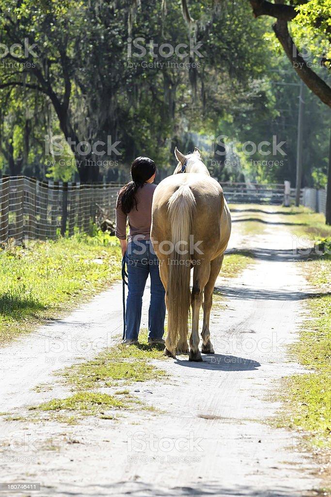 Woman Walking Her Horse Along a Dirt Path stock photo