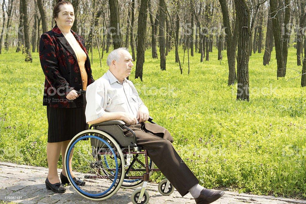 Frau zu Fuß Ihr Mann in seinem Rollstuhl – Foto