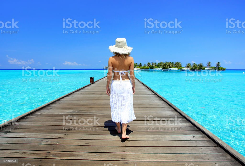 Woman walking in a bridge on the azure water royalty free stockfoto