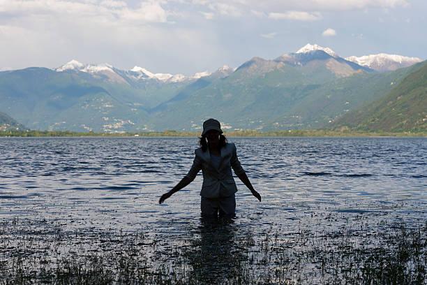 Woman walking in a flooding alpine lake stock photo