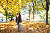 Young cute caucasian woman walking in a park. Autumn time.