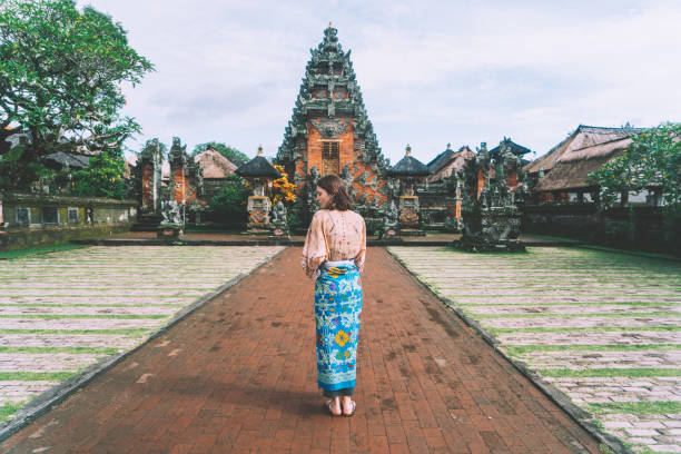 woman walking in balinese temple - традиционная церемония стоковые фото и изображения
