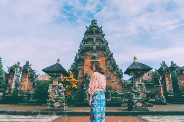 Woman walking in Balinese temple stock photo