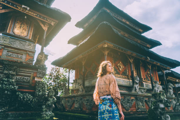 woman walking in balinese temple - travel destinations stock photos and pictures