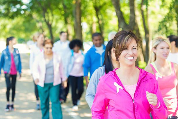 frau zu fuß in breast cancer awareness charity-rennen veranstaltung - rosa training stock-fotos und bilder