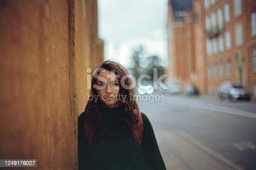 Young Caucasian woman in green sweater with backpack walking in Copenhagen