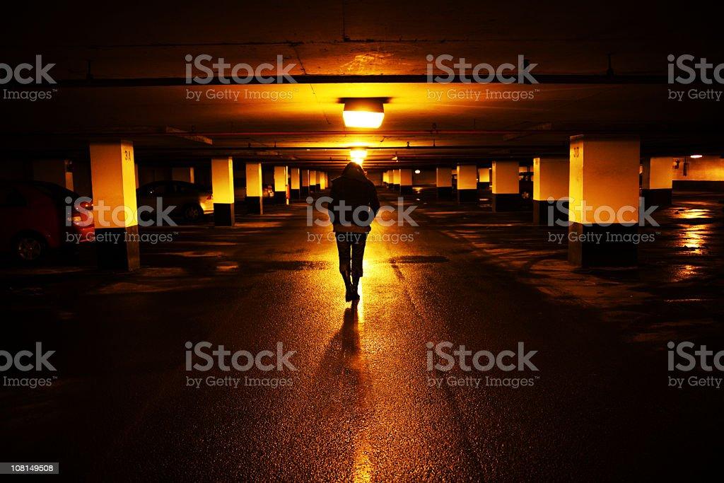 Woman Walking in Dark Parking Garage stock photo