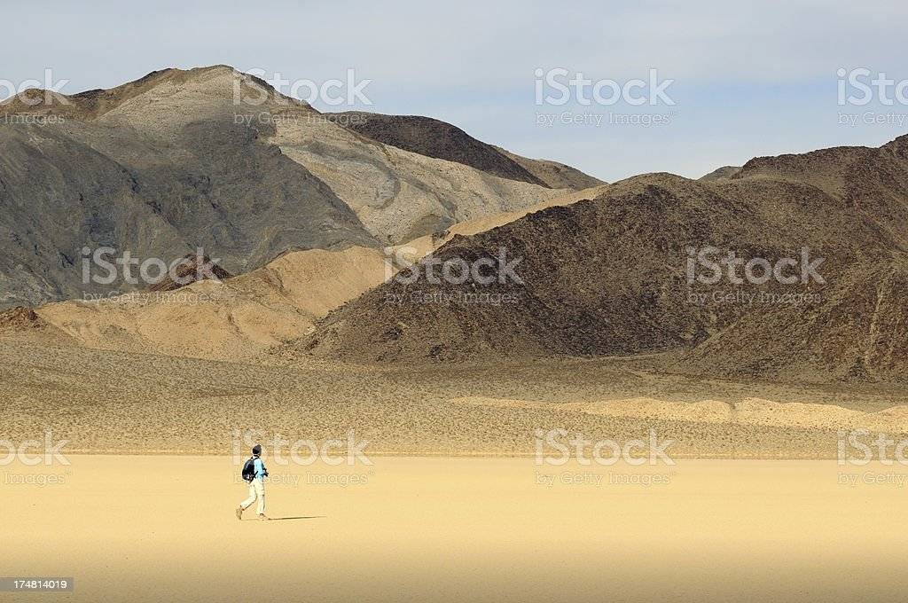 Woman walking in desert near Cottonwood Mountains, Death Valley, USA stock photo