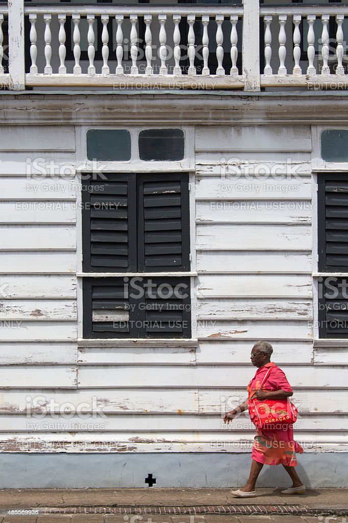 Woman walking in front of a white wooden historic building stock photo