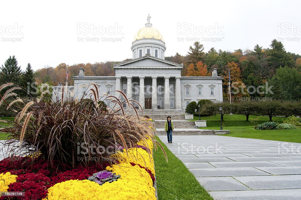 Woman walking in front of the Vermont Statehouse stock photo