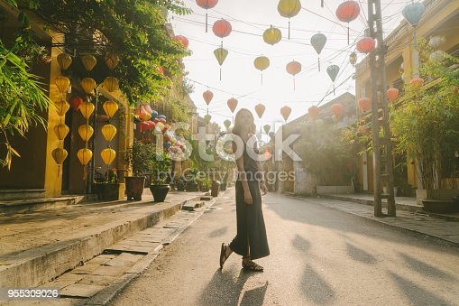 istock Woman walking in Hoi An in the morning 955309026