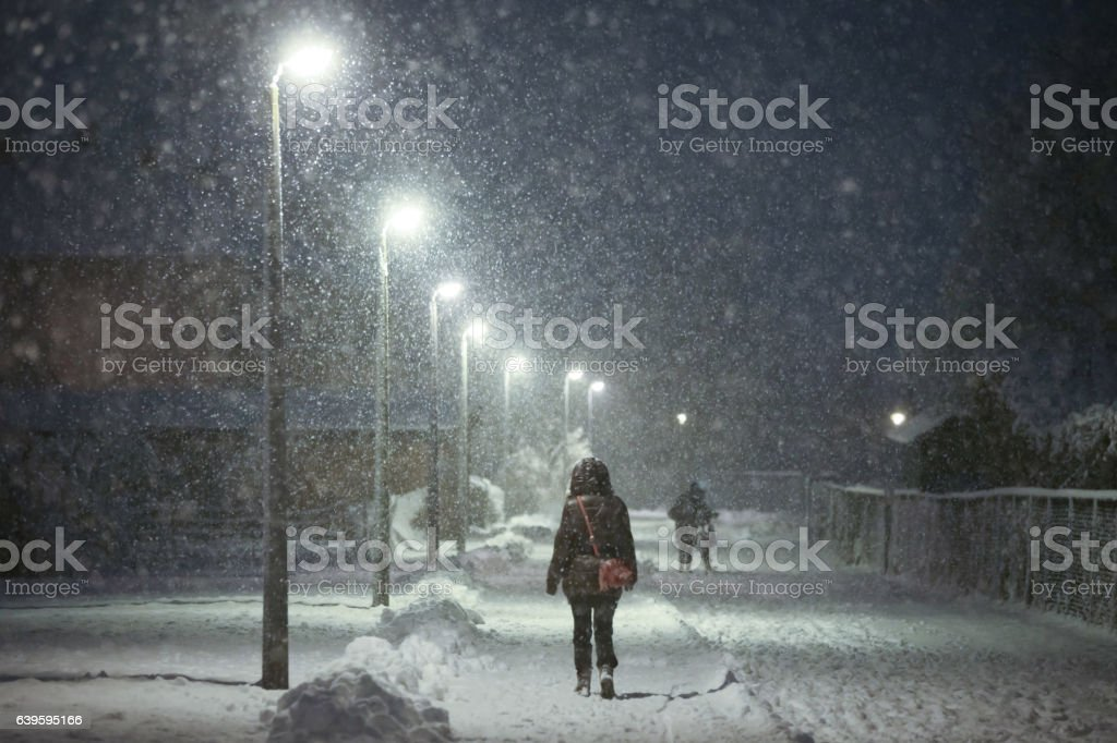 Woman walking in snowy street stock photo