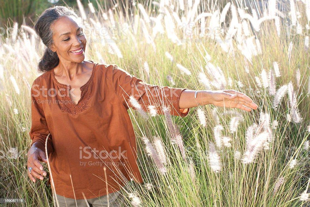 Woman walking in sunny field stock photo